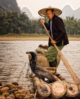 cormerant fisherman paddling raft