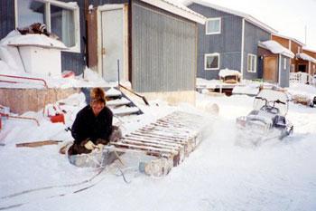 Inuit man repairing sled