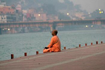 man meditating on steps above river