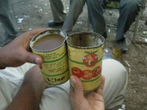 drinking tella out of old tin cans