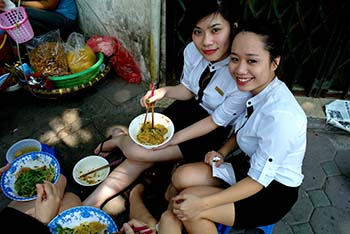 women eating lunch on street