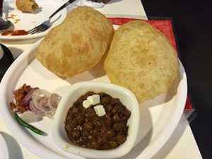 A plate of Chhole Bhature with a side of pickles, onions and green chili