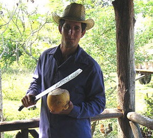 farmer opening coconut with machete