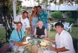 the author and friends cutting a pineapple on Maui