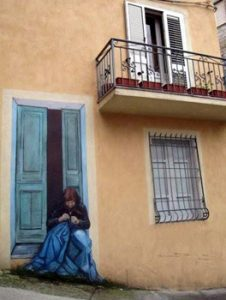 mural of woman in doorway in Orgosolo, Sardinia