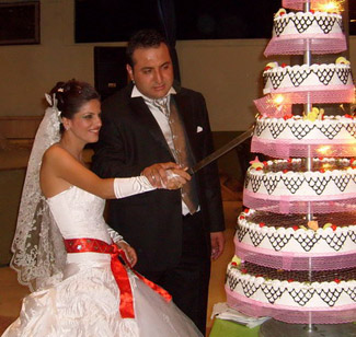 bride and groom cut cake at Turkish wedding