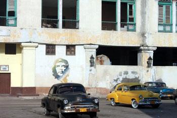 Che Guevara image on wall behind vintage American cars