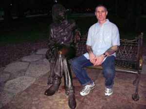 the author sitting alongside John Lennon statue
