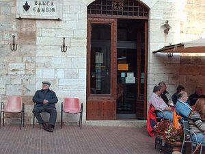 Prato residents on sidewalk outside bank